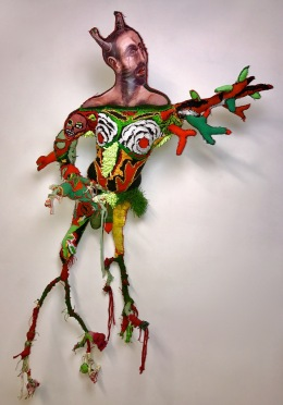 """Daphne"" 2017 Mixed media: acrylic painted recycled rag, embroidery floss,twigs, astroturf, poly-fill. 56 by 33 by 9 inches."