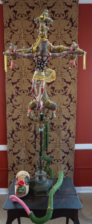The Anchorite's Cross 2019 Mixed media: acrylic painted canvas, recycled fiber, beads, bells, embroidery floss, poly-fil, vintage furniture and metal work, vintage fabric. Cross 60 by 32 by 10 inches approximately; total installation variable upon site.