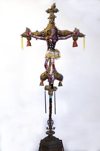 The Anchorite's Crucifix 2019 Mixed media: acrylic painted canvas, recycled fabric, beads, bells, embroidery floss, black pipe interior structure, poly-fil, vintage furniture, metal work and fabric. 60 by 32 by 10 inches, Crucifix only; total installation varies upon situation.